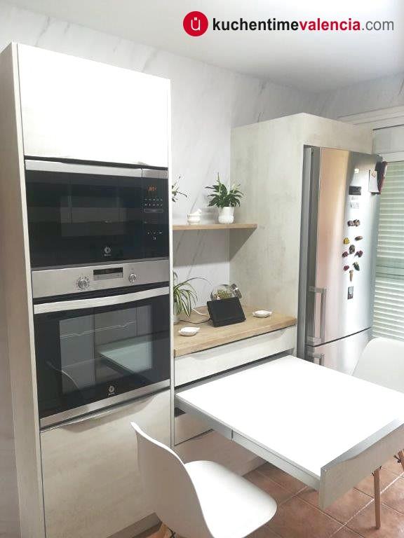 Detalle de columna, mesa ocultable y frigorífico en cocina sin obras